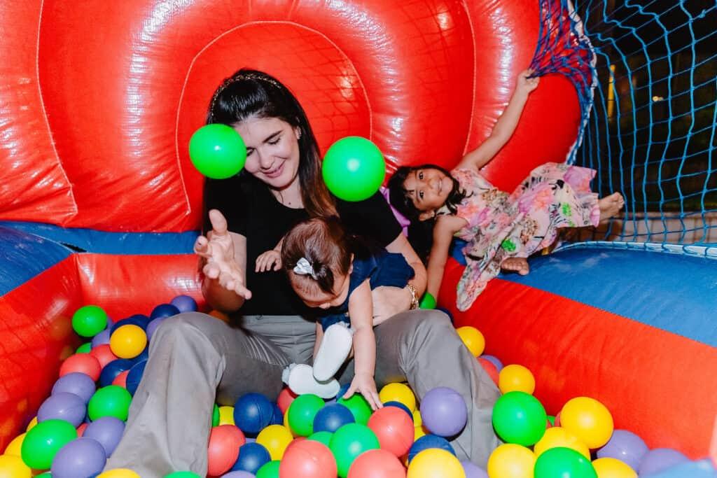 Mãe e crianças brincando na confraternização da Mobills
