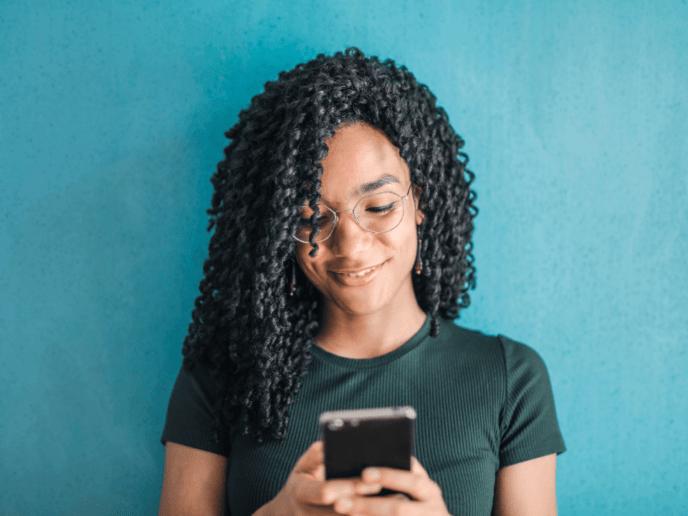 Imagem de uma jovem usando seu celular para acessar os melhores apps de controle financeiro