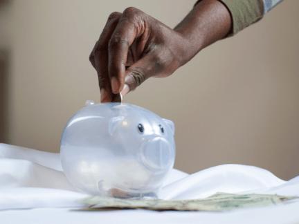 Imagem de uma pessoa em um cofrinho aprendendo como juntar dinheiro