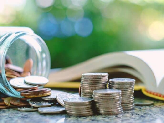 Livro com moedas ao redor simbolizando a educação financeira