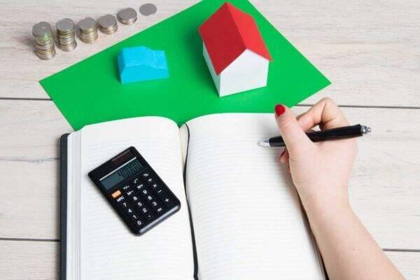 Pessoa escrevendo suas despesas fixas e variáveis em um caderno