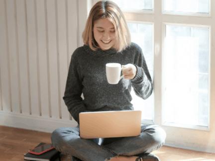 Imagem de uma jovem usando o computador para fazer seu planejamento financeiro pessoal