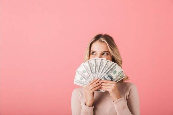 Mulher com dinheiro representando o tema como conseguir dinheiro rápido