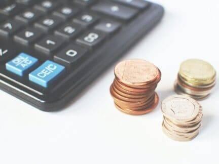 Calculadora e moedas simbolizando como reduzir despesas de casa