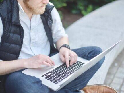 Imagem de uma pessoa usando o computador para ver a planilha de gastos mensais