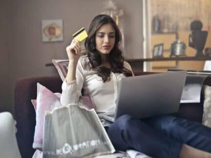 Mulher com sacolas de compras e cartão representando compra por impulso