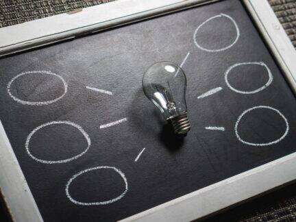 Imagem de um quadro com uma lâmpada e balões representando dicas para organizar suas finanças pessoais