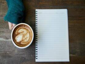 Imagem de um café e um caderno representando o tema hábitos para uma carreira de sucesso