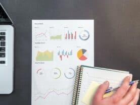 Imagem de um caderno e bloco de notas com gráficos representando os melhores investimentos para 2021