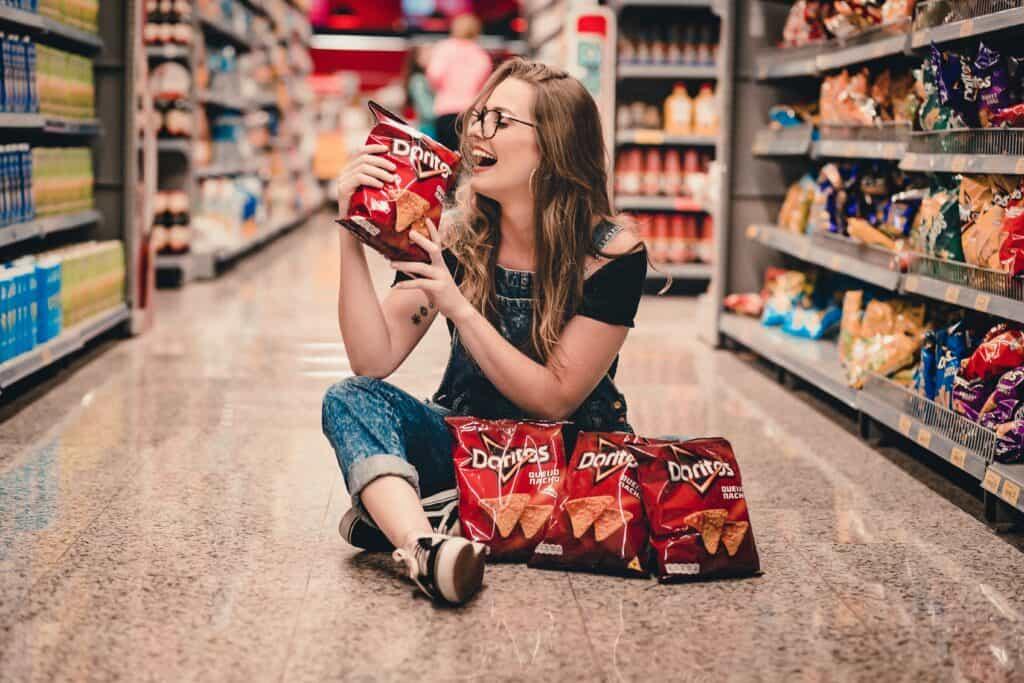 Pessoa no chão de um supermercado com pacotes de salgados