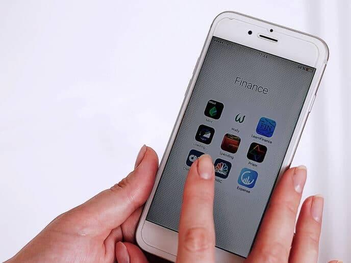 Mão segurando celular com aplicativos representando o tema melhores aplicativos de finanças pessoais para 2021