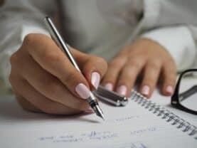 Mulher fazendo uma lista com dicas financeiras para 2021