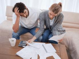 Casal pensando nas finanças representando o tema: dicas de controle financeiro pessoal