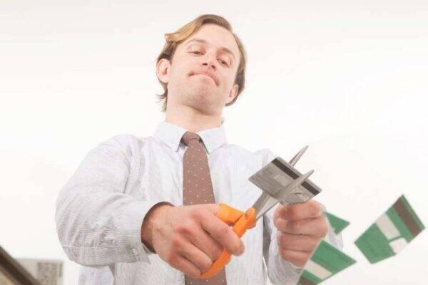 Homem cortando cartões representando o tema como negociar dívidas
