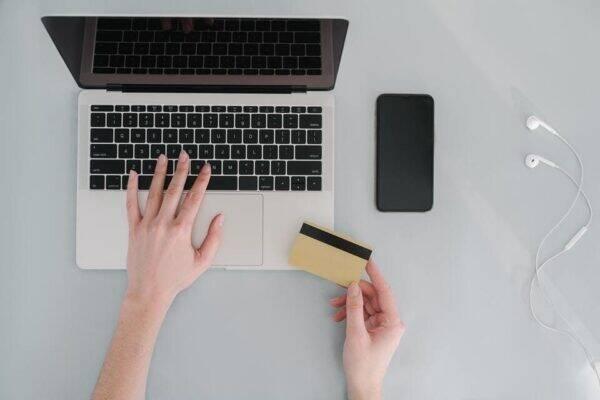 Imagem de uma pessoa com um cartão e computador representando o tema limite do cartão de crédito