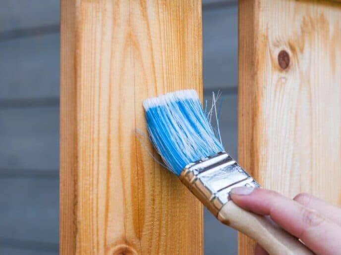 Pessoa pintando um pedaço de madeira representando a técnica diy