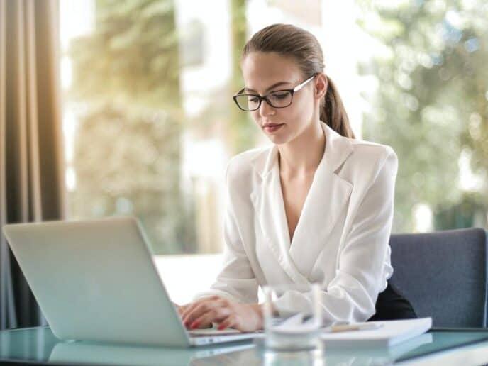 Mulher mexendo em um computador representando atitudes de pessoas bem-sucedidas