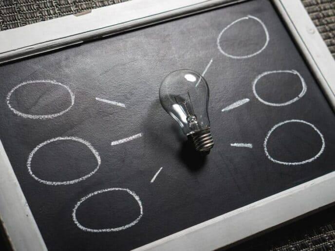 Imagem com uma lâmpada e balões representando funcionalidades do Mobills