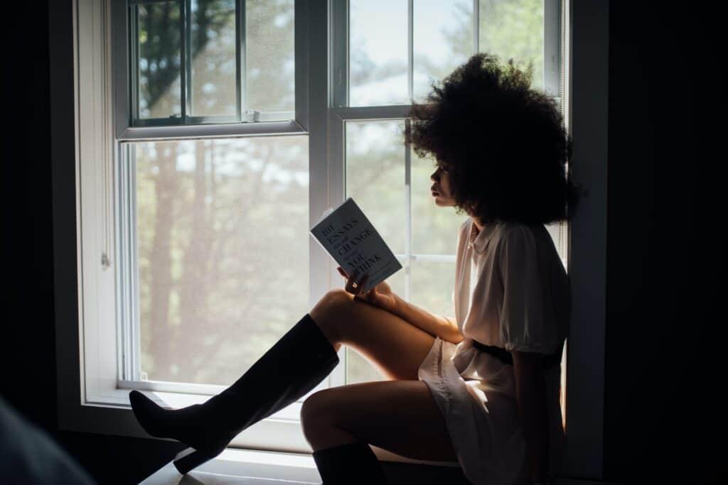 Pessoa lendo o livro representando material escolar barato