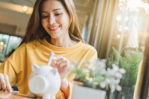 Imagem de uma mulher guardando dinheiro representando o desafio das 52 semanas