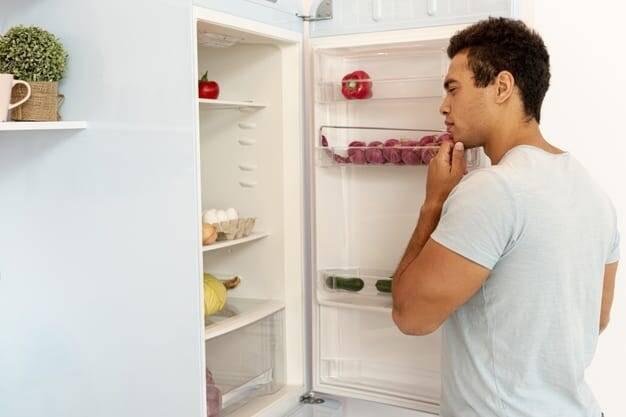 Pessoa com a porta da geladeira aberta