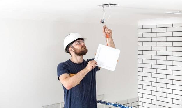 Pessoa trocando uma lâmpada para economizar energia