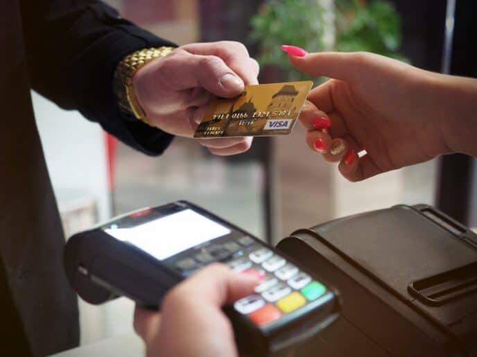 Imagem de uma pessoa passando o cartão de crédito representando o cartão itaucard click