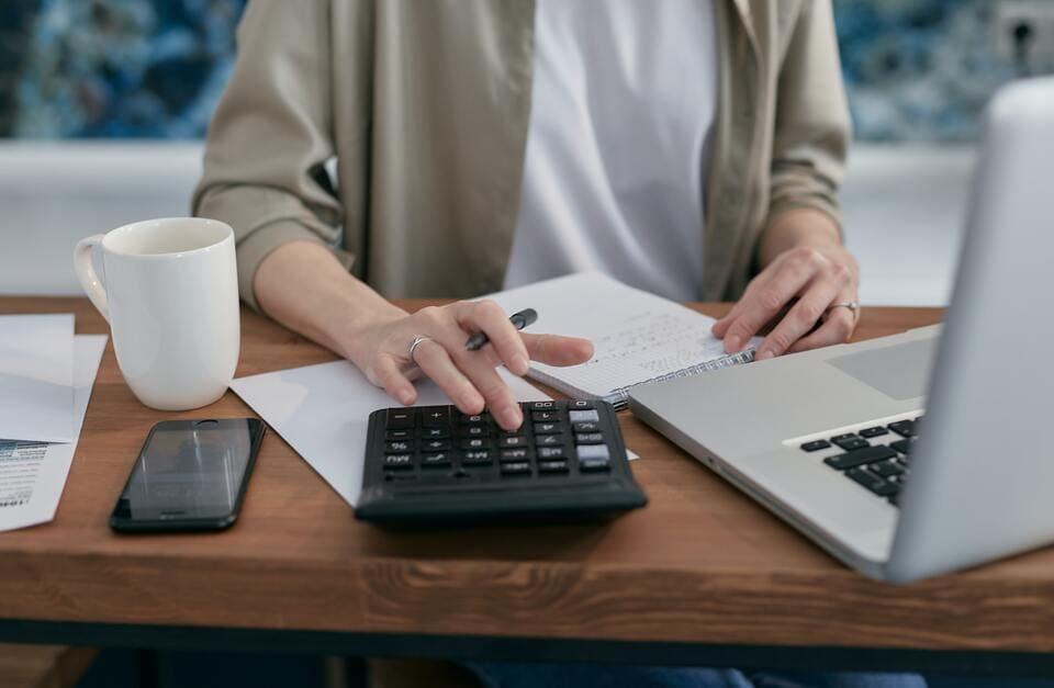 Pessoa calculando como organizar as finanças para aumentar o limite do cartão