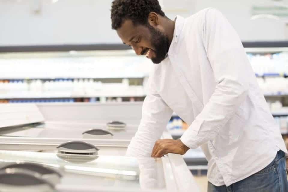 Homem utilizando freezer do jeito correto para economizar energia