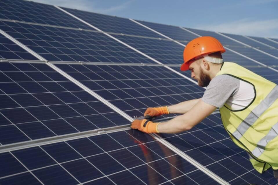 Homem instalando sistema de energia fotovoltaica para economizar gastos com energia