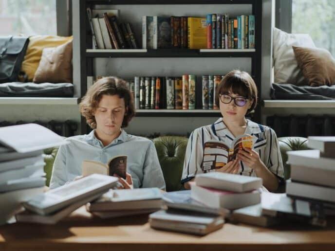 Duas pessoas lendo livros de investimentos