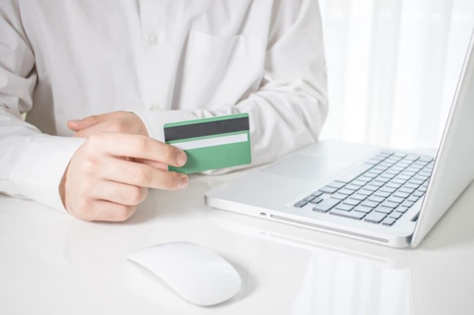 Homem usando cartão de crédito com responsabilidade para contribuir na pontuação do score