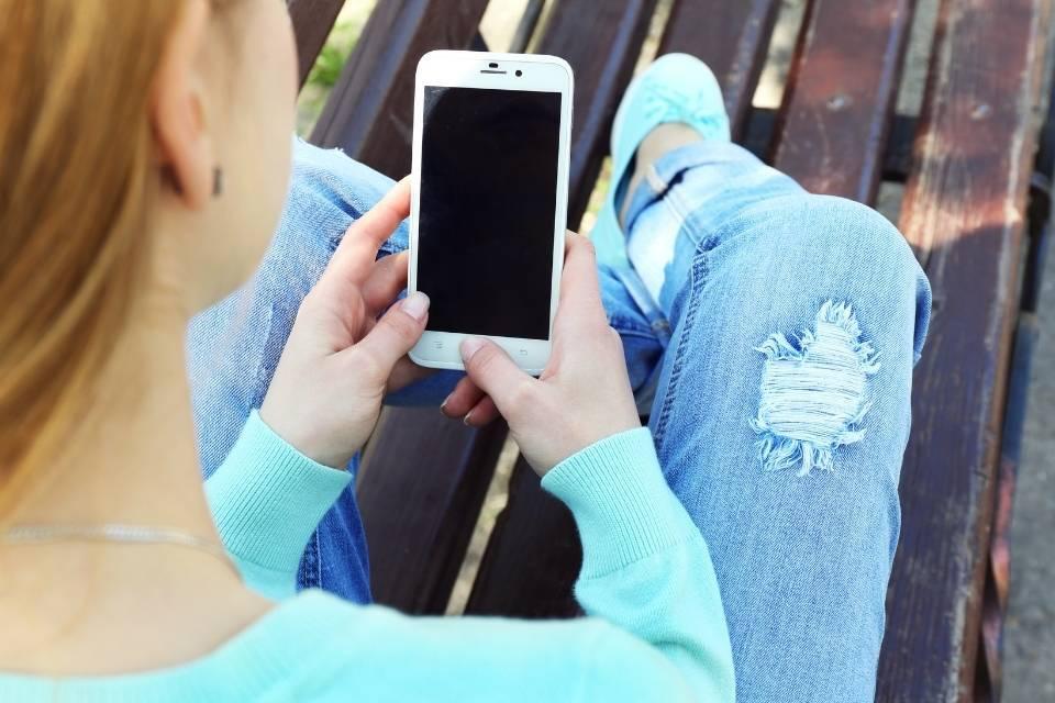 Mulher segurando o celular representando o tema aplicativos para mulheres