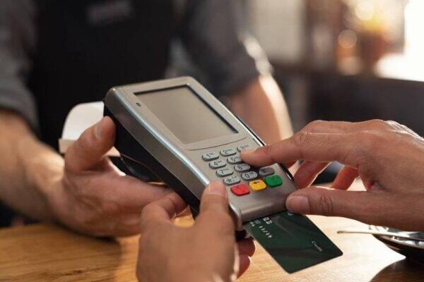 Pessoa utilizando um cartão com cashback