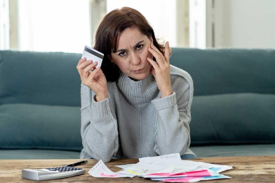 Mulher preocupada com as dívidas no cartão de crédito