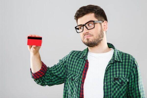Homem tentando descobrir onde fica o cvv do cartão