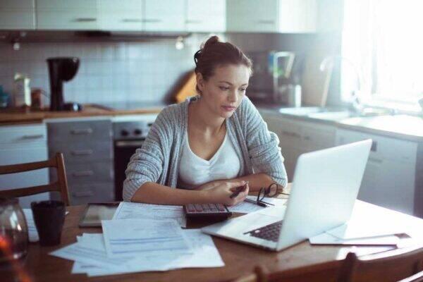 Mulher pensando em como renegociar dívidas online