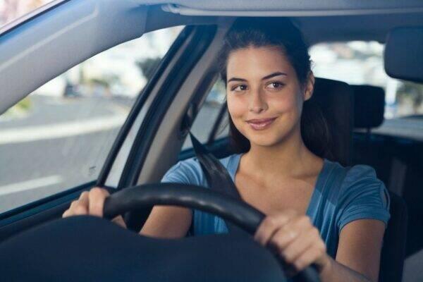 Mulher dirigindo carro com Seguro Auto