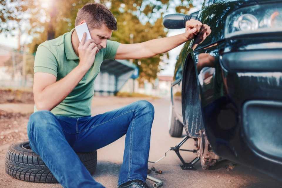 Homem aciona assistência de seguro auto para troca de pneu